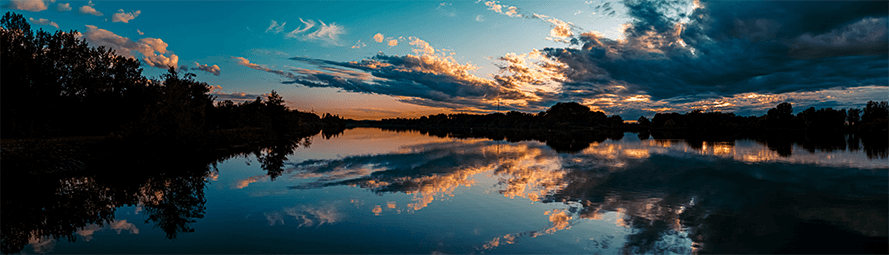 sunset view of landscape with lake, trees, and clouds